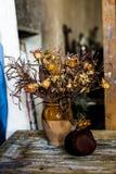 Zusammensetzung eines Vase füllte mit verwelkten Blumen und einem Granatapfel Lizenzfreie Stockbilder