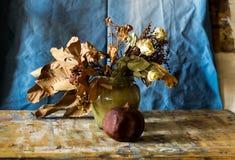 Zusammensetzung eines Vase füllte mit verwelkten Blumen und einem Granatapfel Stockfotos