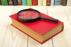 Zusammensetzung mit Büchern und Lupe des gebundenen Buches auf dem Tisch Zurück zu Schule kopieren Sie Raum Scheren und Bleistift Lizenzfreie Stockfotos