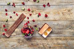 Zusammensetzung mit Blumenblatt-, Weihrauch- und Aromakerze auf hölzernem Brett Stockfotografie