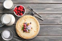 Zusammensetzung mit dünnen Pfannkuchen, Milch, Zuckerpulver Stockbild