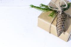 Zusammensetzung mit der Geschenkbox verziert mit Kiefernniederlassungen Stockfotografie