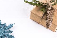 Zusammensetzung mit der Geschenkbox verziert mit Kiefernniederlassungen Stockfoto