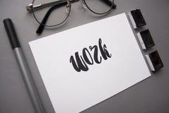 Zusammensetzung mit der Wortarbeit geschrieben in Kalligraphieart, Zwischenlage, schwarzes Aquarell, Gläser auf grauem Hintergrun stock abbildung