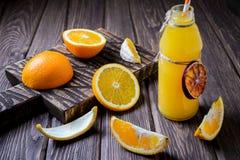 Zusammensetzung mit Flasche Orangensaft und Früchten Stockfoto