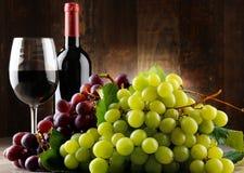 Zusammensetzung mit Glas, Flasche Rotwein und frischen Trauben stockfoto