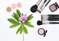 Zusammensetzung mit Make-upkosmetik, -bürsten, -shadoes und -blumen auf weißem Hintergrund Stockfoto