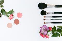 Zusammensetzung mit Make-upkosmetik, -bürsten, -shadoes und -blumen auf weißem Hintergrund Stockfotos