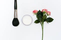 Zusammensetzung mit Make-upkosmetik, -bürsten, -shadoes und -blumen auf weißem Hintergrund Lizenzfreies Stockbild