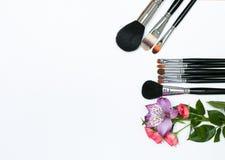 Zusammensetzung mit Make-upkosmetik, -bürsten und -blumen auf weißem Hintergrund Stockfotografie