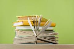 Zusammensetzung mit offenem Buch, gebundenes Buch reserviert auf Holztisch- und Grünhintergrund Zurück zu Schule Scheren und Blei Stockbilder