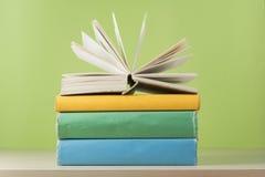 Zusammensetzung mit offenem Buch, gebundenes Buch reserviert auf Holztisch- und Grünhintergrund Zurück zu Schule Scheren und Blei Stockfotografie