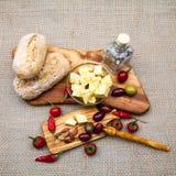 Zusammensetzung mit olivgrünem Holz, Oliven, Brot, Käse bessert im Olivenöl, Gewürze aus Stockbild