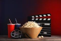 Zusammensetzung mit Popcorn, Kino clapperboard und Filmrolle auf tabl stockfotografie