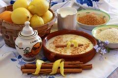 Zusammensetzung mit Reispuddingbestandteilen auf gestickter Tischdecke Stockfotografie