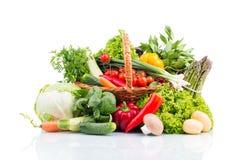 Zusammensetzung mit rohem Gemüse im Weidenkorb auf whi Stockfotos