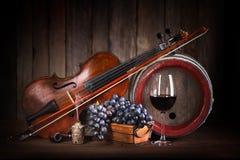 Zusammensetzung mit roter Traube, Wein, Violine und Fass Stockfotos