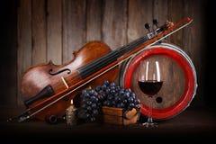 Zusammensetzung mit roter Traube, Wein, Violine und Fass Stockfotografie