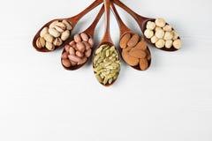 Zusammensetzung mit Samen und sortierten Nüssen auf den hölzernen Löffeln Stockfotos