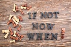 Zusammensetzung mit Schach und Phrase ist nicht jetzt Wann? verfasst von den Buchstaben auf Holztisch Schmutz-Hintergrund f?r Ihr lizenzfreie stockbilder