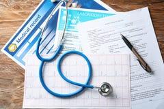 Zusammensetzung mit Stethoskop und Dokumente auf hölzernem Hintergrund Stellen Sie sch?tzende Schablone und die Pille gegen?ber,  stockfotografie