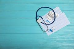 Zusammensetzung mit Stethoskop und Pillen auf hölzernem Hintergrund Kardiologieservice Lizenzfreie Stockfotos