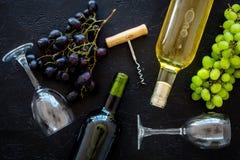 Zusammensetzung mit Weinflaschen Rot und Weißweinflaschen, Weintraube, Korkenzieher, Weingläser auf schwarzem Hintergrund lizenzfreies stockfoto