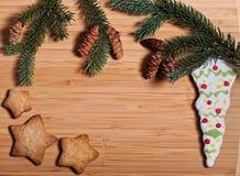 Zusammensetzung neues Jahr ` s von Keksen und von Tannenzweigen auf einem hölzernen Hintergrund Lizenzfreie Stockfotos