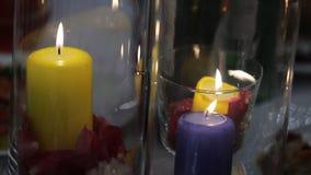 Zusammensetzung von Blumenblumenblättern und von brennenden Kerzen steht auf festlicher Tabelle stock footage