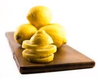 Zusammensetzung von frischen und geschnittenen Zitronen auf einem hölzernen Brett und einem weißen Hintergrund Stockfotografie