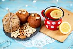 Zusammensetzung von Keksen, von Tasse Tee und von Zitrone auf dem Weinlesehintergrund Lizenzfreie Stockfotos