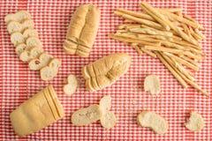Zusammensetzung von Laiben und von Breadsticks über roter und weißer Kontrolleurtischdecke mit Brot schneidet Ansicht von oben Stockfotos