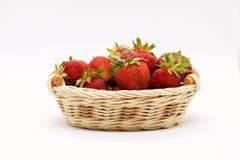Zusammensetzung von reifen Erdbeeren auf einem weißen Hintergrund in einem Weidenkorb stockfotos