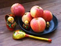 Zusammensetzung von roten und gelben Äpfeln auf schwarzer Roheisenplatte mit traditionellem russischem Verschachtelungspuppen mat lizenzfreies stockfoto