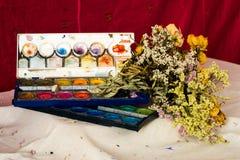 Zusammensetzung von verwelkten Blumen und von Aquarellen Stockfotos