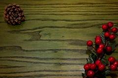 Zusammensetzung von Weihnachten-pinecone, Niederlassungen von Hollies auf grünem hölzernem Hintergrund lizenzfreie stockfotos