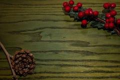 Zusammensetzung von Weihnachten-pinecone, Niederlassungen von Hollies auf grünem hölzernem Hintergrund stockbilder