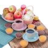 Zusammensetzung von zwei Kaffeetassen, von kleinen Kuchen, von Eibischen und von appl Stockfotos