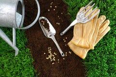 Zusammenstellung der Gartenhilfsmittel auf Erde Lizenzfreie Stockfotos