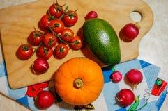 Zusammenstellung des Frischgemüses - Tomatenzucchini-Kürbisrettich Herbstgemüse auf Schneidebrett und Tuch lizenzfreie stockfotos