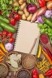 Frischgemüse und leeres Rezeptbuch Stockfoto