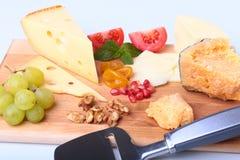 Zusammenstellung des Käses mit Früchten, Trauben, Nüssen und Käsemesser auf einem hölzernen Umhüllungsbehälter Stockbild