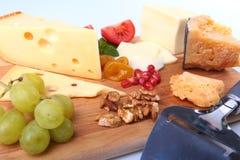 Zusammenstellung des Käses mit Früchten, Trauben, Nüssen und Käsemesser auf einem hölzernen Umhüllungsbehälter Stockfoto