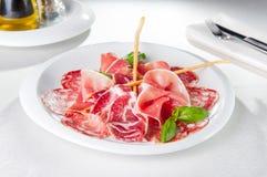 Zusammenstellung des kalten italienischen Fleisches, der Salami, des Schinkens und des Speckes der Delikatessen auf Teller Stockbild