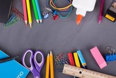 Zusammenstellung des Schulbedarfs auf einem Tafel-Hintergrund Lizenzfreies Stockbild