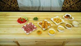 Zusammenstellung von den geschmackvollen Mahlzeiten, die auf großem Holztisch erscheinen stock footage