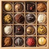 Zusammenstellung von feinen Pralinen, von Weiß, von Dunkelheit und von Milchschokolade im Kasten Bonbons Hintergrund, Draufsicht stockbild