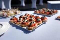 Zusammenstellung von geschmackvollen Aperitifs - Canapes, Sandwiche auf der weißen Tischdecke lizenzfreies stockfoto