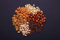 Zusammenstellung von Nüssen auf einem schwarzen Hintergrund - gesunder Snack Stockfoto