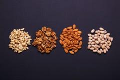 Zusammenstellung von Nüssen auf einem schwarzen Hintergrund - gesunder Snack Stockbilder